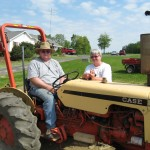 A photo of a man on a tractor and woman beside him.