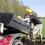 Students unload a load of mulch in the garden.