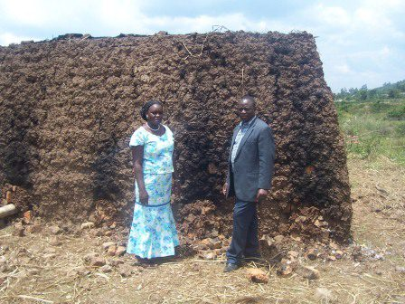 Rev. Abanga and his wife stand in front of the bricks.
