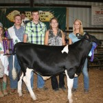 This year's grand champion dairy beef feeder, raised by Madison Malloy, sold for $2.20 a pound to Kiko Auctioneers, represented by Pam and Ryan Kiko. Also pictured are fair royalty Curtis Veiock and Melinda Richey.