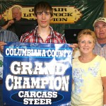 (Farm and Dairy photo) Brent Reisner raised the grand champion carcass steer, which sold for $1.75 a pound to Jeff and Sheryl Hoopes for their family's use.