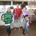 Hunter Urmson raised the 144-pound reserve champion market lamb, which sold for $4.50 a pound to Chesapeake Energy, represented by Jesse Redwine. Also pictured is Hannah Swope, Columbiana County Sheep and Wool Ambassador.