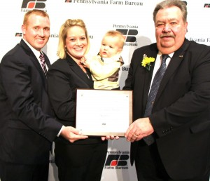 Cambria County farmers Tommy and Tracy Nagle, along with their young son Brady, receive Pennsylvania Farm Bureau's 2013 Young Farmer and Rancher Achievement Award during PFB's 63rd Annual Meeting in Hershey. Presenting the award is PFB President Carl Shaffer (right).