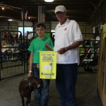 Corey Soulek's 82-pound grand champion goat sold to the Summit County Farm Bureau, represented by Tim Walsh, for $225 a head.