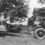 (Submitted by Art Smallsreed)This photo, taken in July 1942, shows the first combine on the Smallsreed farm, in Braceville Township, after years of using a custom threshing machine and help from neighbors. Glenn Smallsreed is on the tractor, Glenn's children Miriam and Arthur (on seat) are on the bagging platform. In 1963, Glenn and Arthur incorporated the farm business as Glen-Art Farms, Inc.