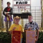 Michael Miller's pen of 26.34-pound reserve champion and reserve best of show chickens garnered a $28.00 a pound bid from Bonnie Plizga, of B.P. Enterprise.  Also pictured is 2014 Ashtabula Junior Fair Prince Zachary Conoby (right).