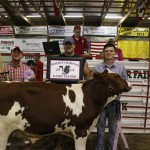 Logan Skolosh received a $6 a pound bid from Bishop Construction, Inc. for his 580-pound reserve champion dairy feeder.  Pictured from left are Mark Skolosh, Mark Bishop, and Logan Skolosh.