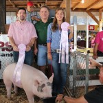 Paige Lewis sold her 278-pound reserve champion hog for $20 a pound to Paris and Washington Insurance and Dutchcraft Truss & Metal Inc/Pole Barns Direct.  Pictured from left are Reggie Stoltzfus of Dutchcraft Truss & Metal Inc/Pole Barns Direct, Kelly Palmer of Paris and Washington Insurance, and Paige Lewis.