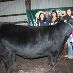 Kyla Sharp sold her 1,278-pound reserve champion steer for $5.60 a pound to Mac Trailer, represented by Rachel (left) and Jenny Conny. Sharp was also the Outstanding Youth Project grand champion.