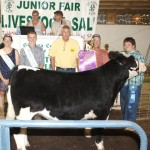 Jacob Carver's 1,316-pound grand champion steer sold for $6.50 a pound to Oscar Brugmann Sand & Gravel, represented by Todd Brugmann. Also pictured are fair royalty Josh Loveland and Kelli Briggs.