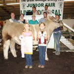 Chris and Julie Clemson paid $5.75 a pound for Nicole Rider's 1,214-pound reserve champion steer. Also pictured are fair royalty Josh Loveland and Kelli Briggs.